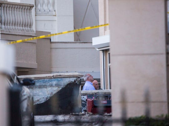 Crime scene investigators and Naples police look up at the Club Brittany building in Naples, where two construction workers fell to their deaths on Wednesday, May 9, 2018.