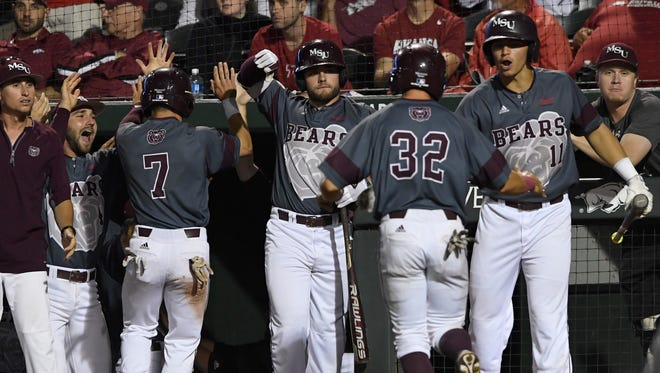 Missouri State's Hunter Steinmetz (7) and John Privitera (32) are greeted by teammates Logan Geha (4), Blake Graham, center, and Jeremy Eierman (11) after scoring two runs against Arkansas in the third inning of an NCAA college baseball regional tournament game in Fayetteville, Ark., Sunday, June 4, 2017.