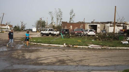Residents evacuate the town after a tornado severely damaged the area Monday, June 16, 2014, in Pilger, Neb. The National Weather Service said at least two twisters touched down within roughly a mile of each other.
