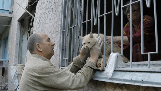 A man takes his cat from his damaged house after shelling in the city of Slovyansk, eastern Ukraine.