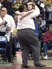 Fort Defiance's Jeff Weeks hugs his coach, Terry Waters, after  winning the 103-pound Group AA state championship in 2003.