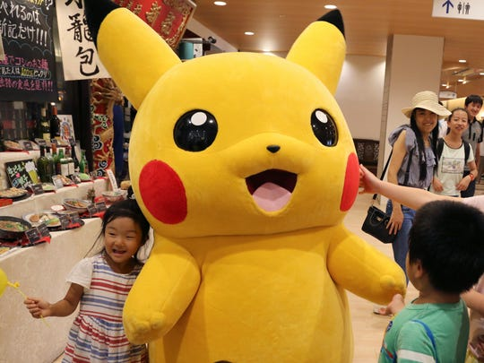 Pikachu is surrounded by children during a Pokemon