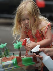 """Annie Dorrington sprays water on a watershed model at the new """"green street"""" project in midtown Ventura."""