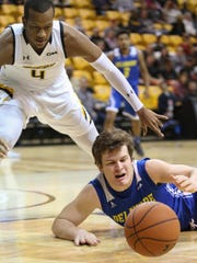 Delaware guard Ryan Daly dives for a loose ball in front of Towson's Justin Gorham in the first half of the Blue Hens' 67-65 loss at Towson.