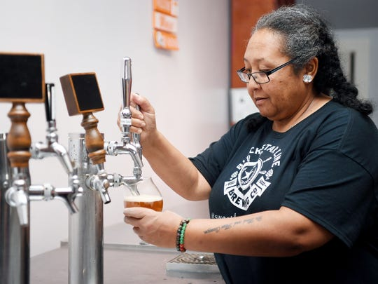 Tina Marshall pours a glass of Black Star Line's pale ale October 23, 2017 in Hendersonville.