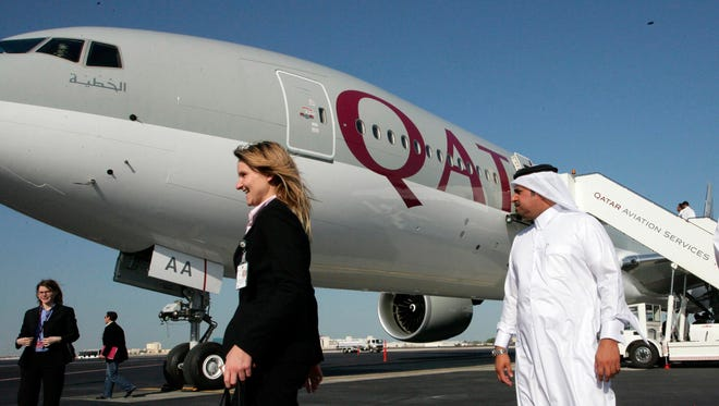 Staff members walk past the first-ever Boeing aircraft 777 delivered to the state-owned Qatar Airways at Doha airport on Nov. 29, 2007.