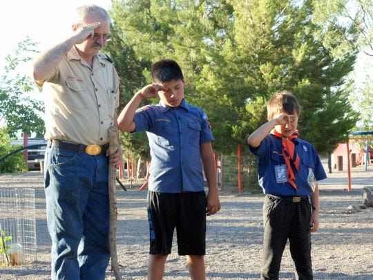 Scout Master Randy Jones and two Deming Cub Scouts honor the flag during its retirement ceremony.