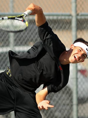 Palm Desert's Alex Kuperstein serves the ball to Indio's Eleazer Vazquez during a boys varsity tennis match on Tuesday, April 7, 2015 at Indio High School.