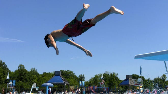 Alex Bourgeois, 11, of Mason, gets a big dive off the board at the Lou Eves Municipal Pool in Mason.  The Enquirer/ Liz Dufour
