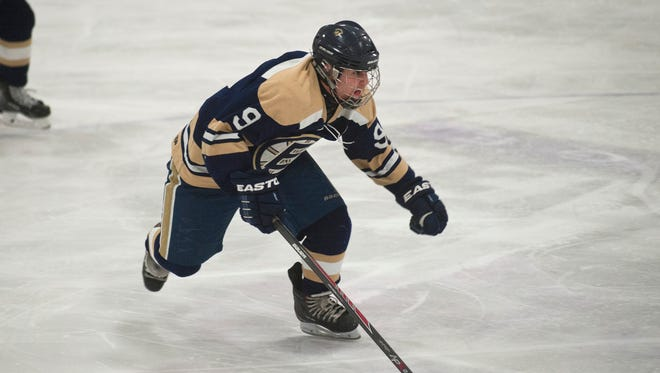 Essex's Zac Godin skates up the ice with the puck during the third period of Saturday's boys hockey game against Champlain Valley at Cairns.