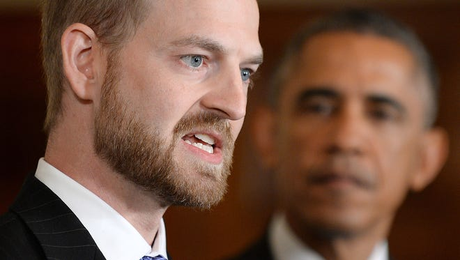 Ebola survivor Dr. Kent Brantly speaks about the heroic work of health care workers caring for Ebola patients as President Barack Obama looks on during an event in the East Room of the White House on Wednesday, Oct. 29, 2014, in Washington, D.C. (Olivier Douliery/Abaca Press/MCT)