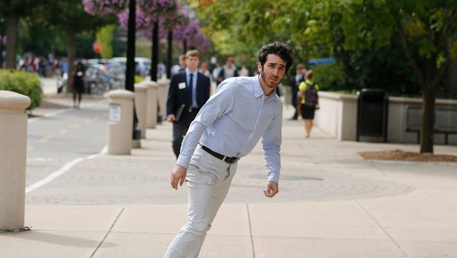 Joe Carabetta rides his electric skateboard Tuesday, Sept. 17, 2013, through the campus of Purdue University. Carabetta, a senior, and Evan Merz, also a senior, designed the electric skate board, which can travel 8-10 miles on a charge.