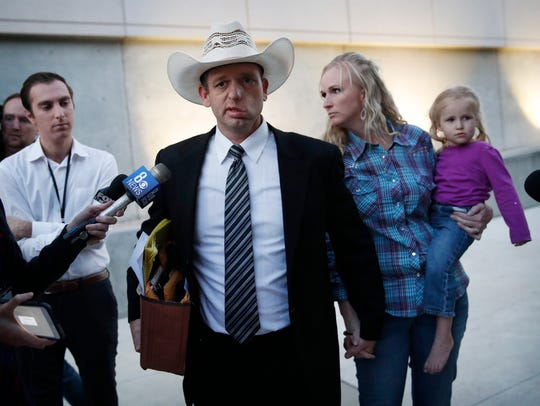 Ryan Bundy, center, walks out of federal court with
