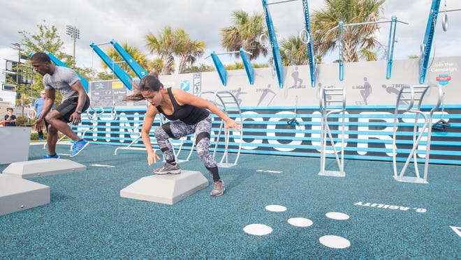 Dionte, of Regymen Fitness, and Elvie Perrault, of Pensacola Fitness & Legendary Fitness, go head to head in a workout during the new free outdoor bodyweight circuit training fitness center launch party at Vince J. Whibbs Sr. Community Maritime Park in Pensacola on Friday, April 27, 2018.