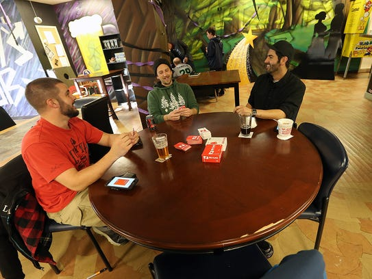 From left, Matt Constantino, Joshua Gratton and John Gonzalez play a card game called Red Flags while enjoying their drinks.