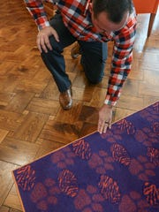 Mike Garren of Harris Flooring America in Anderson looks at carpet and the wood tile floor in the office of head coach Dabo Swinney, inside the Clemson Football Facility on Friday.