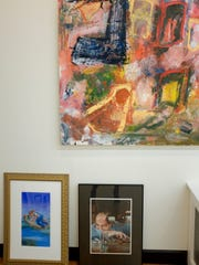 Small works by Robert Hochgertel waiting to be hung, sitting below a painting by Chuck Hosier.