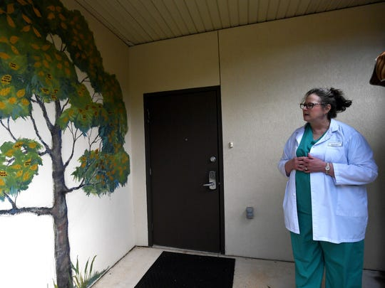 Brenda Mires, a registered nurse and director of clinical services at Mountain Area Pregnancy Services, looks at a painted tree bearing names of babies lost to miscarriage, still birth, newborn death or abortion.