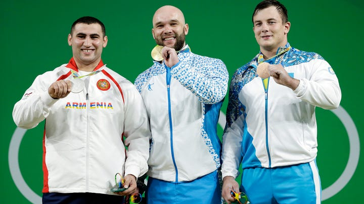 File - In this Monday, Aug. 15, 2016 file photo, Ruslan Nurudinov, of Uzbekistan, center, holds his gold medal as he is joined by silver medalist Simon Martirosyan, of Armenia, left, and bronze medalist Alexandr Zaichikov, of Kazakhstan, right, during the medal ceremony for the men's 105 kg weightlifting event at the 2016 Summer Olympics in Rio de Janeiro, Brazil. Nurudinov has been disqualified from the 2012 London Games for doping with an anabolic steroid. The Court of Arbitration for Sport says its new anti-doping chamber stripped Nurudinov of fourth place in London in the 105-kilogram weight class. The 27-year-old lifter from Uzbekistan now faces a ban from the International Weightlifting Federation. (AP Photo/Mike Groll, File)