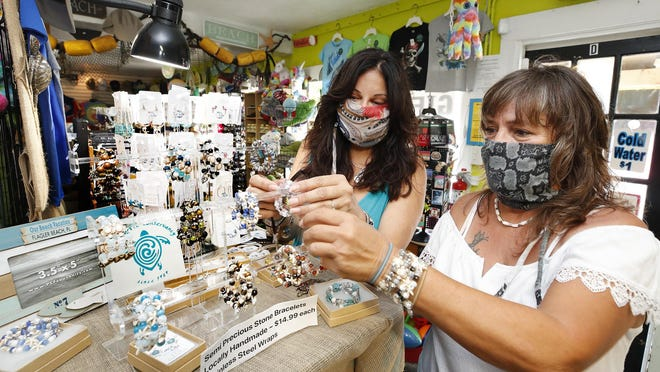 Michelle Brown, owner of Flagler Beach Gift Shop along with Mary O'Neill, right, working at the shop in Flagler Beach, Thursday, July 23, 2020.
