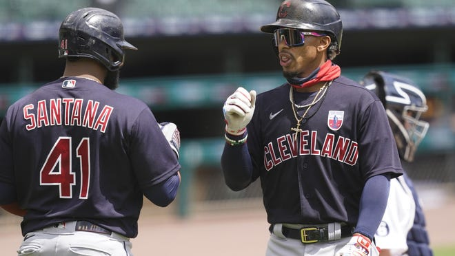 Cleveland Indians' Francisco Lindor, right, is greeted at home plate by teammate Carlos Santana after hitting a two-run home run during the third inning of a baseball game against the Detroit Tigers, Sunday, Aug. 16, 2020, in Detroit.