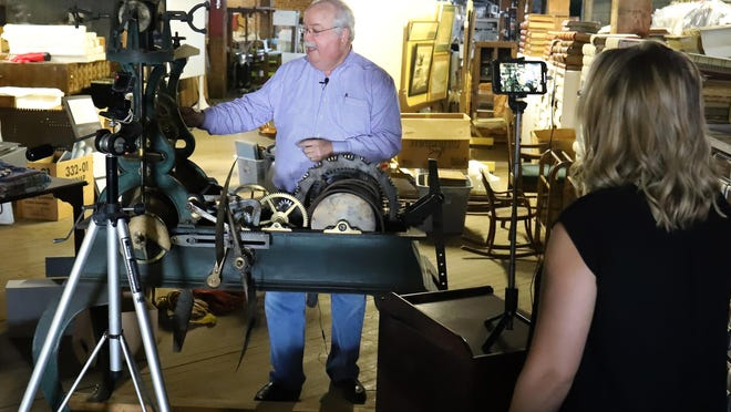 """Chuck Girard, Fort Smith Museum of History collections manager, talks about the second hand mechanism pulleys and gears in the 1888 Sebastian County Court House clock, Tuesday, August 4, 2020, as FSMH board member Amanda Hager records the presentation for the upcoming FSMH """"Un-Masked,"""" un-event, September 26, 2020. Caroline Speir, FSMH executive director, said that the un-attend fundraiser is in respect of social distancing and offers museum patrons an opportunity to support the museum during the COVID-19 pandemic."""
