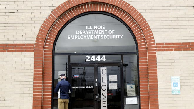A man checks information in front of Illinois Department of Employment Security in Chicago, Thursday, April 30, 2020. Illinois is applying for the $300 weekly unemployment benefits supplement President Donald Trump ordered earlier this month