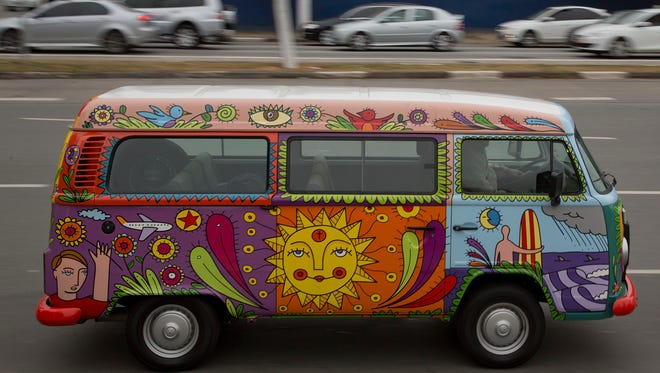 Brazil ad exec Marcelo Serpa has painted his 2007 VW Bus to resemble how the vehicles were adorned in the 1960s by counter-culture hippies. He is shown driving it in Sao Paulo September, 2013. Brazil, the last place the Bus was made, quite in December and the last new ones now are sold.