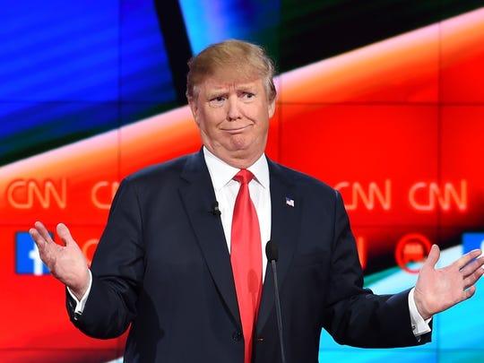 Donald Trump gestures during a GOP presidential debate