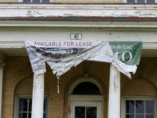 """A faded and ripped """"Available For Lease"""" banner displayed on the front of the YMCA building at Fort Hancock."""