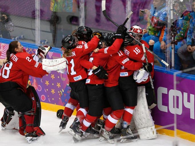 Team Switzerland celebrates defeating Sweden 4-3 in the women's ice hockey bronze medal game.