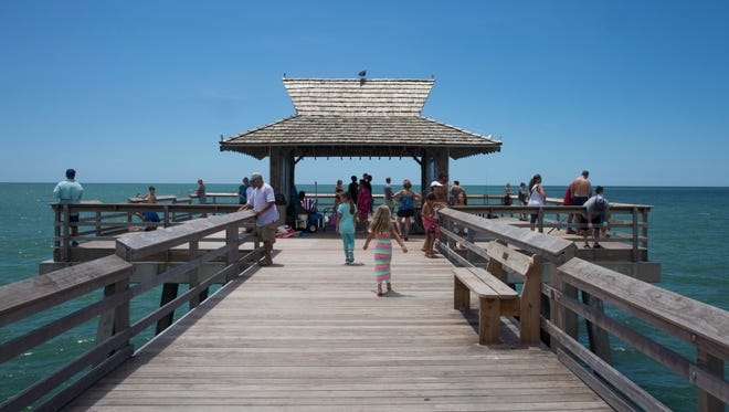 Tourists and locals take in the Gulf of Mexico from the Naples Pier on Aug. 11, 2016, in Naples.