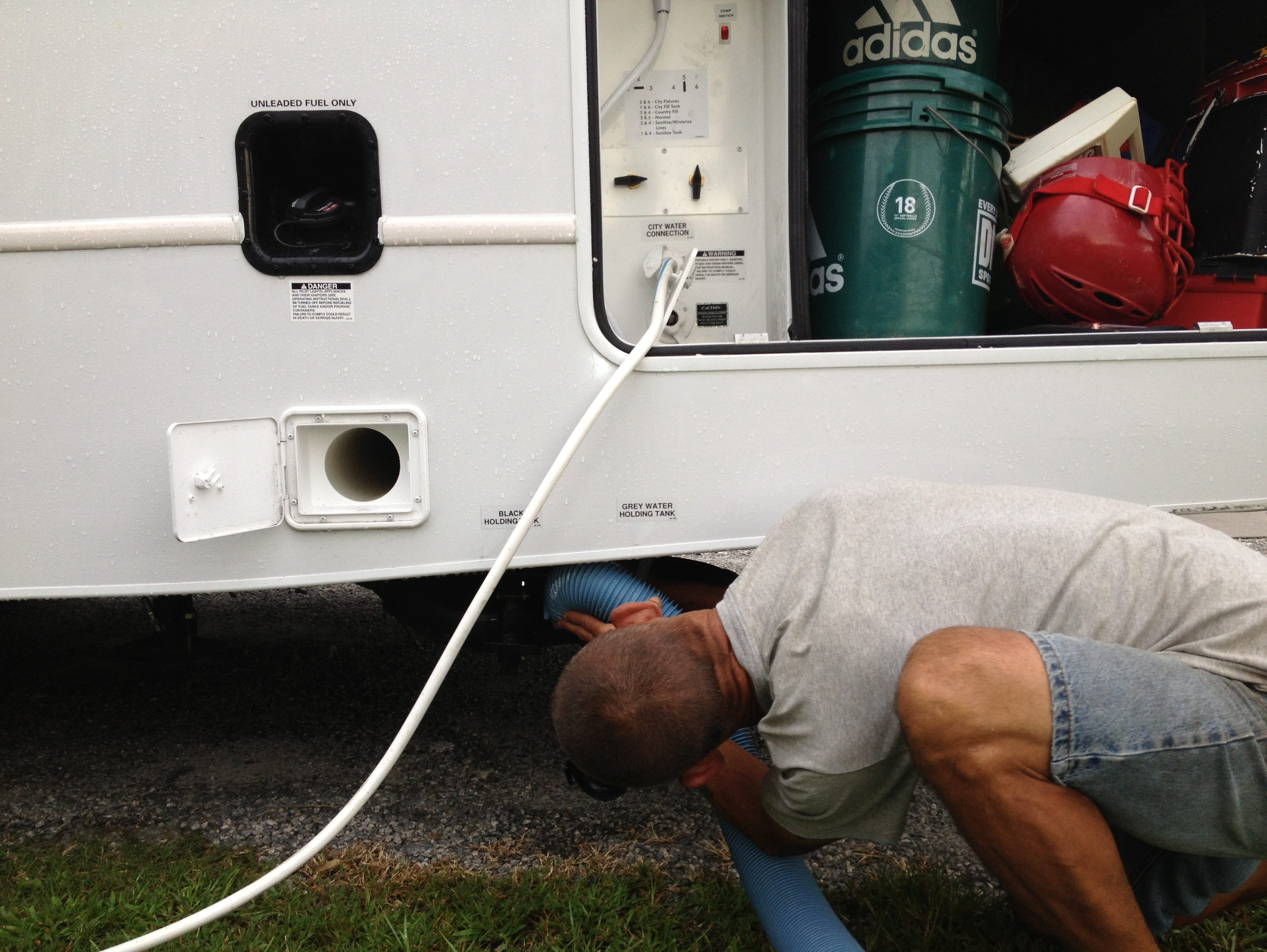 Twin Oaks RV Park Campground co-manager Mike Gannaway prepares to dump the black water (toilet) of O'Donnell's Jayco Greyhawk, after having hooked up the fresh water. Above Gannaway's head is a confusing-for-beginners control panel for the fresh water.
