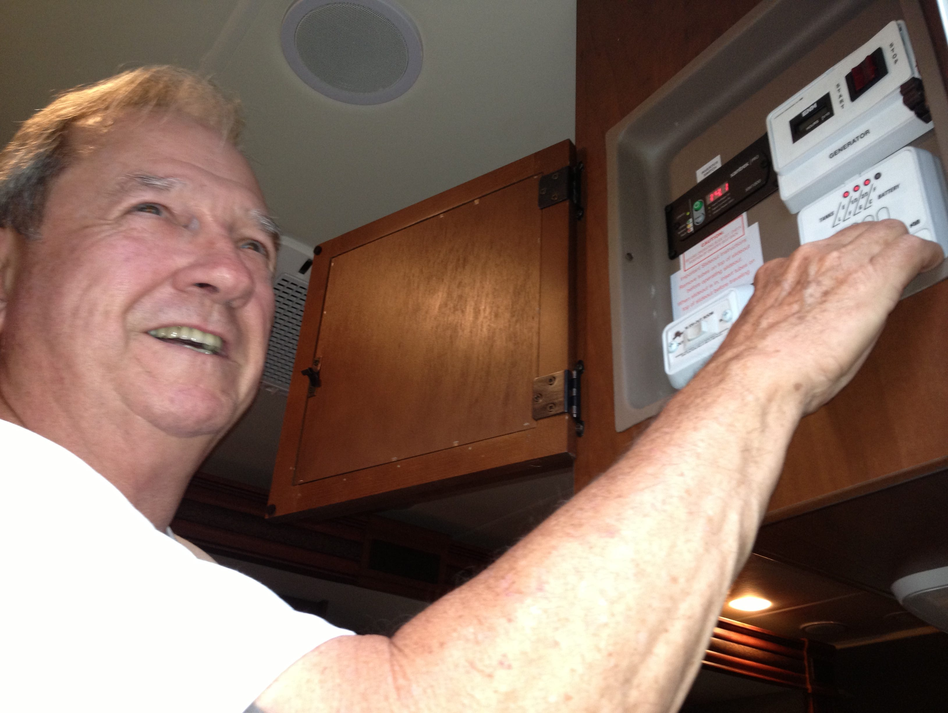 Twin Oaks guest Larry Smith checks the water-tank levels on the RV and gives O'Donnell a primer on how to decipher and work the control panels.