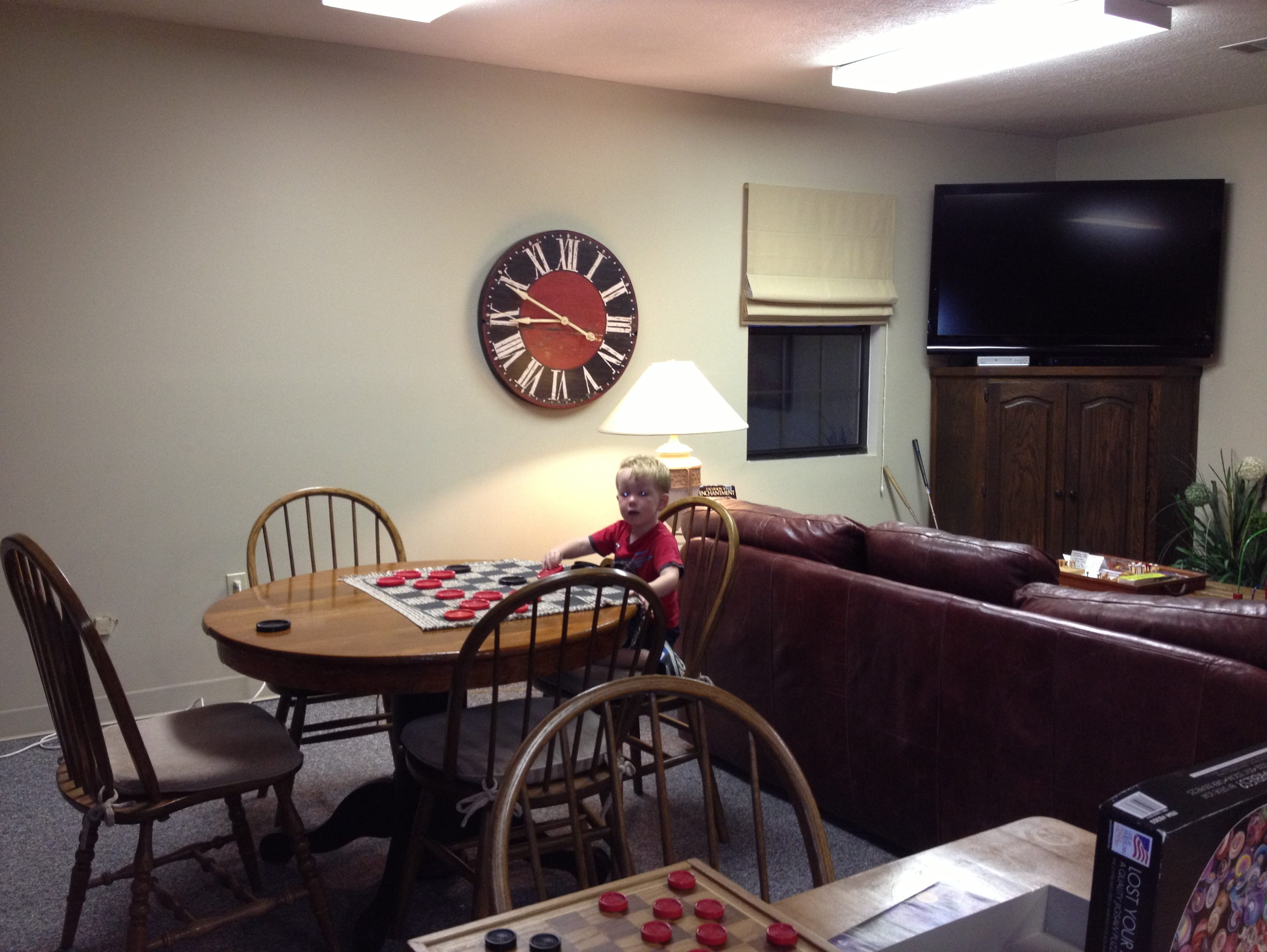 Even young guests can find diversions in the community building. Caleb Schneider entertains himself in the game room with checkers.
