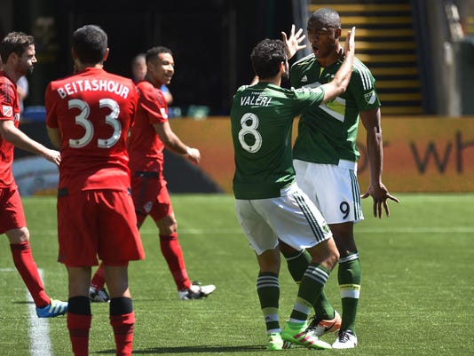 Portland Timbers forward Fanendo Adi (9) celebrates with teammate Diego Valeri (8) after scoring a goal in the first half of an MLS soccer game against Toronto FC in Portland, Ore., on Sunday, May 1, 2016.AP Photo/Steve Dykes)