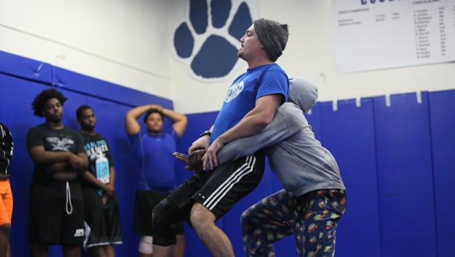 Godby wrestling coach Richard Burkette demonstrates a move for his team to practice on Wednesday afternoon.