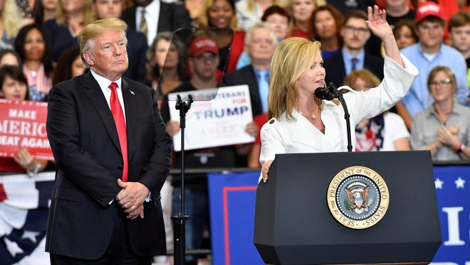 U.S. Senate candidate Marsha Blackburn speaks to the crowd as President Donald Trump looks on during a rally at Municipal Auditorium, Tuesday, May 29, 2018, in Nashville, Tenn.