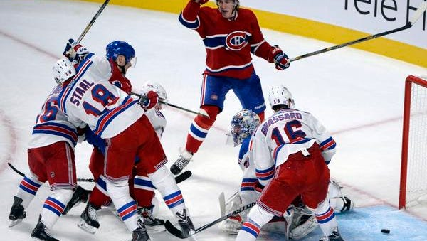 Montreal Canadiens forward Dale Weise, top, reacts after a goal scored by teammate Lars Eller, surrounded by Rangers defenders Marc Staal (18), Mats Zuccarello and Derick Brassard (16).