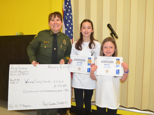"Elise and Adelle Evans, 10 and 8, presented a homemade 'check"" to Undersheriff Susan Schilling."