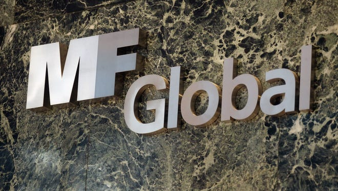 File photo taken in 2011 shows an MF Global sign in the New York City Manhattan office building where the brokerage had offices before its bankruptcy collapse.