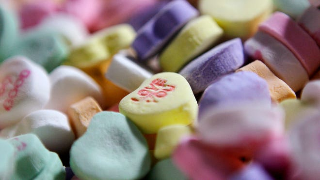 """Colored """"Sweethearts"""" candy is held in bulk prior to packaging at the New England Confectionery Company in Revere, Mass. Four bidders are vying to buy the bankrupt manufacturer of Necco Wafers, Sweethearts and other iconic candies. A bankruptcy auction is scheduled for Wednesday, May 23, 2018."""