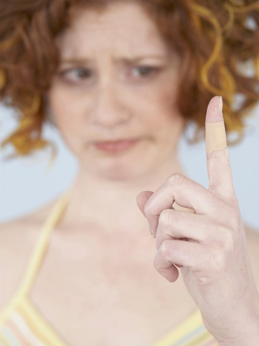 Close-up of mid adult woman looking at bandaged finger