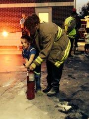Firefighter trainee Deana Coffey helps 4-year-old