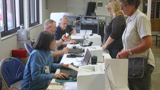 Precinct workers at the Amana precinct of the Clear Creek Amana School District confirm information from voters in the school board election Tuesday, Sept. 12. CCA voters passed a $36 million bond issue and helped usher in two new board members, including one who unseated an incumbent.
