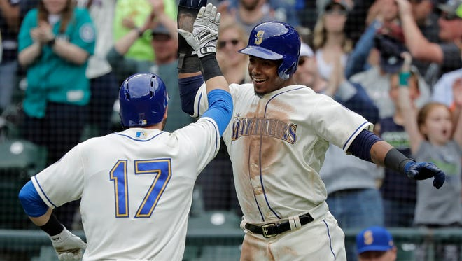 Mitch Haniger (17) and  Jean Segura celebrate after Haniger tied Sunday's game with a two-run home run in the ninth inning. The Mariners won 3-2 in extra innings.