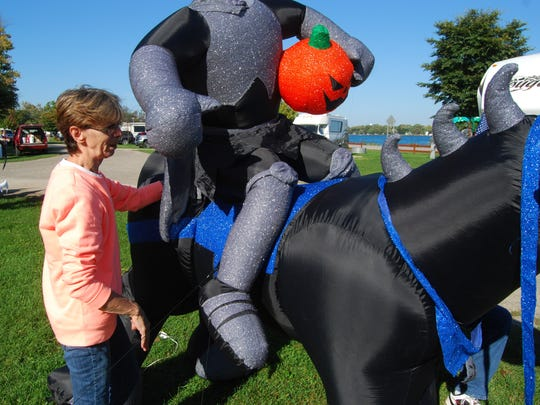 Elva Osieczonek works on a headless horseman inflatable Friday at Algonac State Park.