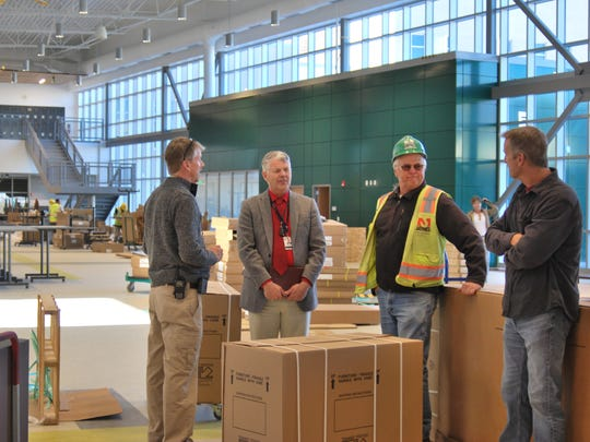 Farmington High School Principal Tim Kienitz, Farmington Municipal School District Superintendent Eugene Schmidt, Jaynes Corp. project superintendent Don Halstead and Jaynes Corp. project manager David Hawthorne have a conversation among unpacked furniture in the new commons of the Farmington High School during a community tour of the new building on Dec. 8.