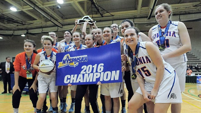 Livonia players pose with a New York State Public High School Athletic Association Class championship banner In Troy.