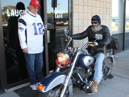 Bernie Munro, president of the New England Patriots Fan Club of Southwest Florida, watches as Storm arrives on his New England Patriots Themed Harley at the Laugh-In Comedy Cafe on Thursday.